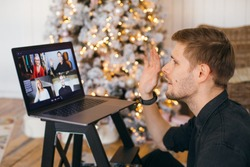 A video call on Christmas morning at home. Man smiling and waving. Christmas tree and lights background. Virtual thanksgiving house party Online team meeting video conference calling from living room