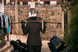 A Vietnamese female scrap collector at Dalat wearing an Asian conical hat, carrying bags using shoulder pole. Translation texts on the right blue canvas bag: