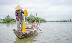 A Vietnamese man fishing with a yellow net in the lake