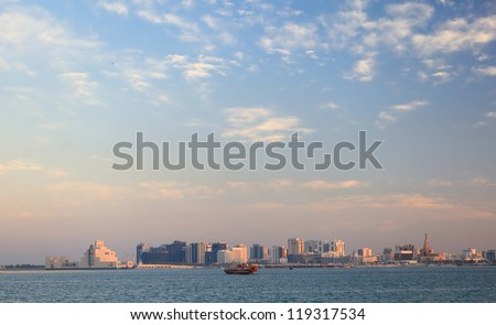 A view across Doha Bay, Qatar, at sunset. The Museum of Islamic Art is to the left of the skyline and the spiral minaret of the Qassim Darwish mosque to the right, with a dhow between.