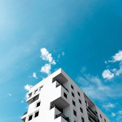 A view at a detail of a modern white apartment building in Lyon, France with blue sky background