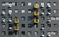 A view at a straight facade of a modern building with a dark grey facade and yellow balconies in Belgrade, Serbia