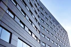 A view at a straight facade of a modern building with a dark grey facade. Dark grey metallic panel facad. Modern architectural details.