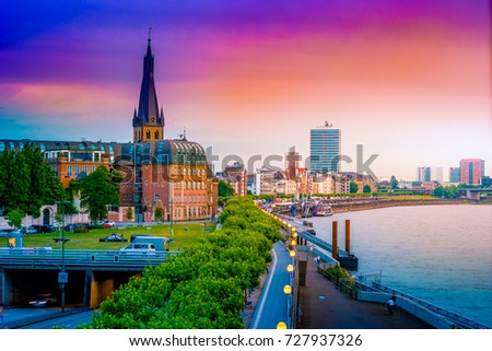 A view at the city skyline central Dusseldorf from the rhine river, Dusselfdorf Germany. Colorful panorama of german city at sunset. #727937326