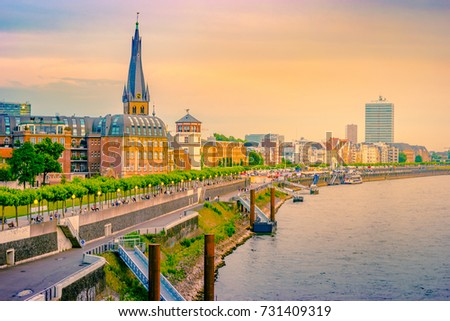 A view at the city skyline central Dusseldorf from the rhine river, Dusselfdorf Germany. Colorful panorama of german city at sunset. #731409319