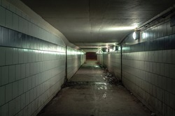 A view down a damp and dirty glazed tiled block and concrete tunnel urban or city pedestrian underpass corridor below Lake Shore Drive in Chicago with white and blue colors and lights on the wall.