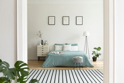 A view from a different room into a pastel bedroom interior with a big bed in the middle and a lamp and a night cabinet beside. Real photo.