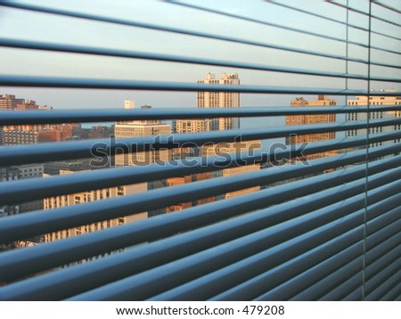 A view from a High rise window over the city of Chicago. Looking through window blinds at a view over the city.