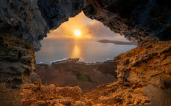 A view from a natural rock cave to the ocean during sunset