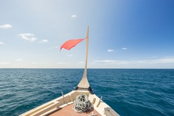 A view from a wooden boat sailing in the sea, clear sky, windy. Maldives.