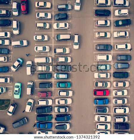 A view from above to the ranks of head-in parked cars.End-to-end parking. Cruising for parking space. Trouble-free navigation in the parking lots. Problem of space for a parked vehicle. Busy parking #1374321392