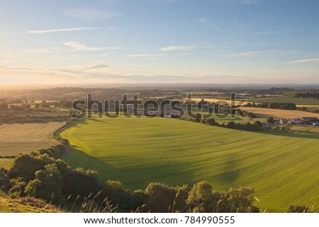 A view from Cley Hill, Wiltshire looking west with views of rural farmland in the evening light as sun begins to set. Stock photo ©