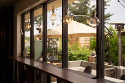 A view from inside a cafe setting, looking through a wall of windows towards a comfortable isolated patio area, featuring vintage hanging lightbulbs.