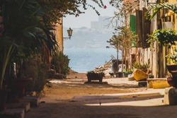 A view from one of the streets on Ille de Goree towards the city of Dakar. Beautiful street on the island of Goree, Senegal.