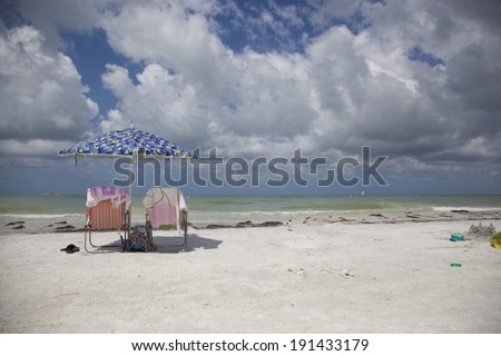 A view from the beach into the Gulf of Mexico from Honeymoon Island State Park in Dunedin, Florida. Two beach chairs are set up with an umbrella in between.