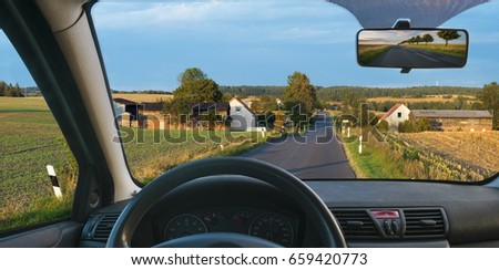 A view from the cockpit of a car driving on a country road