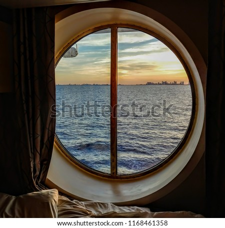 A view from the porthole window of a cruise ship, showing the city buildings in the sunset. The photo was taken inside a cabin on a Caribbean cruise.