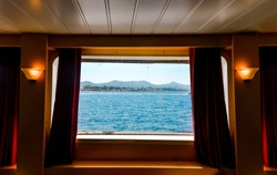 A view from the porthole window of a cruise ship, showing the sea and island.