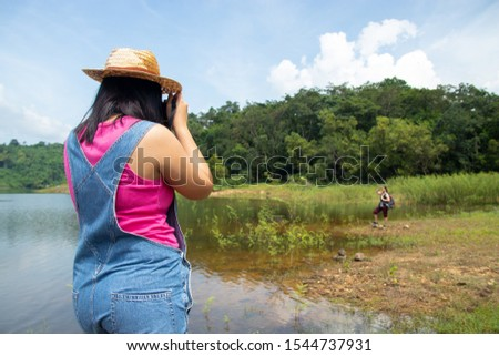 A view from the side of a woman in a coyote with a pink shirt standing, photographing her mother on the edge of a stream that can be seen far away. Concept of tourism and relaxation.
