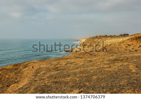 a view from the top of a mountain overlooking the beach and the atlantic sea outside of oualidia, morocco, with a bright sun and sparsely clouded skies #1374706379