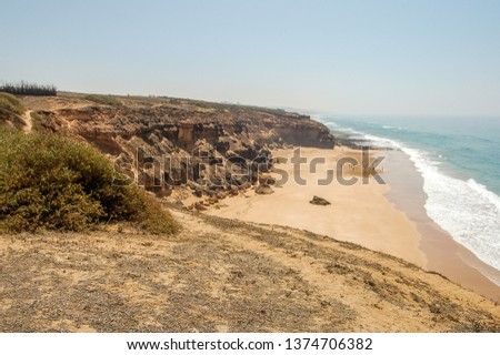 a view from the top of a mountain overlooking the beach and the atlantic sea outside of oualidia, morocco, with a bright sun and sparsely clouded skies #1374706382