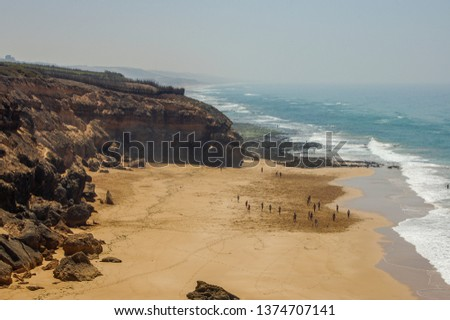 a view from the top of a mountain overlooking the beach and the atlantic sea outside of oualidia, morocco, with a bright sun and sparsely clouded skies #1374707141