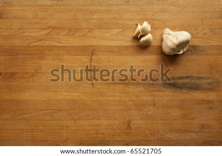 A view looking down on a group of single garlic cloves and a clump of garlic on a worn butcher block cutting board