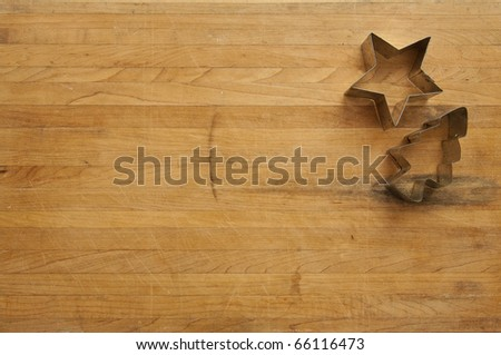 A view looking down on a metal star and tree cookie cutter on a worn butcher block cutting board
