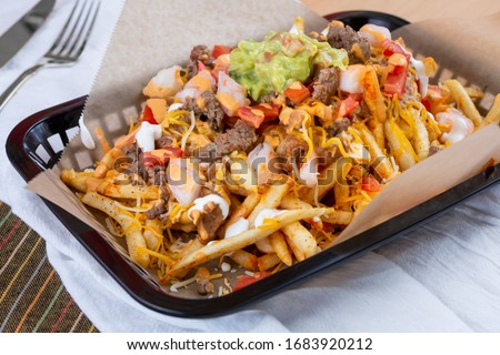 A view of a basket of carne asada fries, in a restaurant or kitchen setting. Foto stock ©