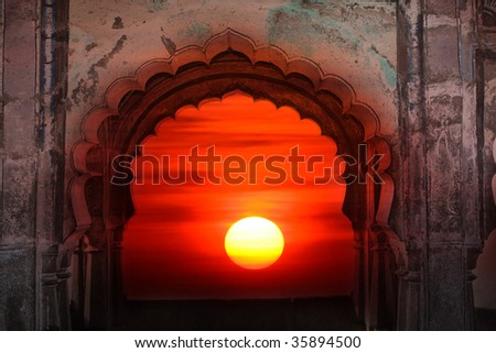A view of a beautiful sunset through an ancient arched window of an Indian fort.