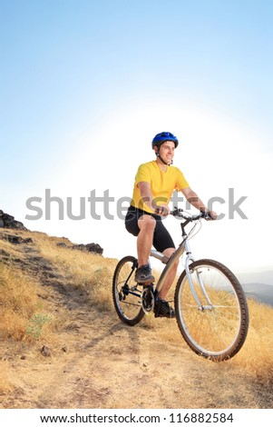 A view of a biker riding a mountain bike on an offroad track