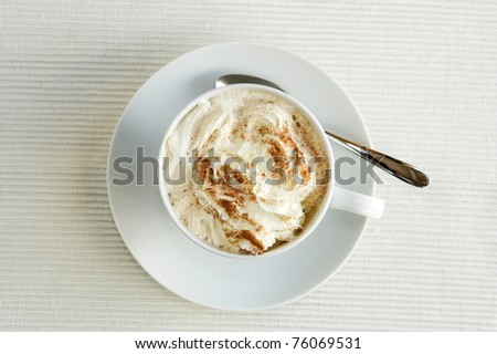 A view of a cappuccino in a white cup, shot from above. The cup is located near a window and shows cream in the cup with sprinkled cocoa on top.