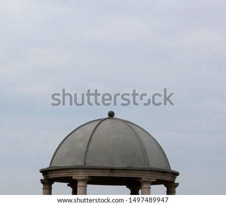 A view of a cement dome and the cloudy overcast sky. #1497489947