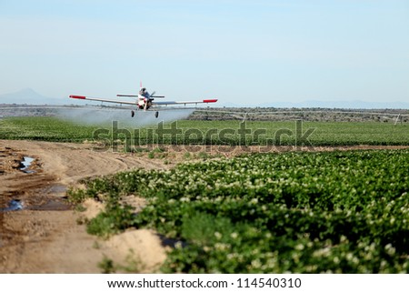 A view of a crop duster spraying green farmland.