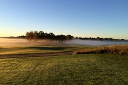 A view of a golf course with a morning September mist.