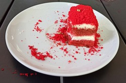A view of a half-eaten slice of red velvet cake on a white plate, layered with whipped cream and red crumble s scattered