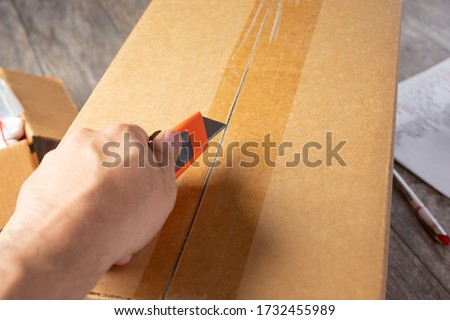 A view of a hand holding a box cutter tool prepping to open a cardboard box shipment package. ストックフォト ©