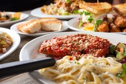 A view of a layout of several prepared entrees, featuring a plate of chicken parmigiana and pasta, in a restaurant or kitchen setting.