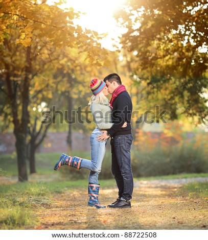 A view of a loving couple kissing in the park in autumn