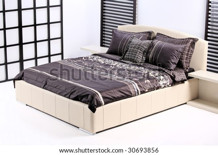 A view of a modern bed in a bedroom - stock photo