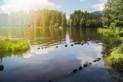 A view of a mountain alpine lake on a summer day. Lake with hills, water and blue sky with clouds. Green forest by the lake in reflection in the water beauty in nature
