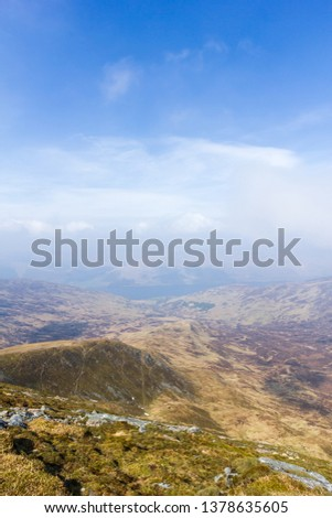 A view of a mountain valley with rocky path,grass and lake in the background under a majestic blue sky and white clouds #1378635605