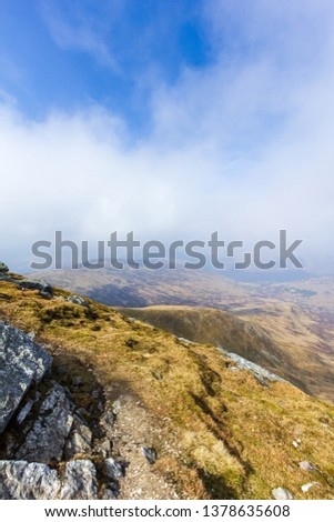 A view of a mountain valley with rocky path,grass and lake in the background under a majestic blue sky and white clouds #1378635608