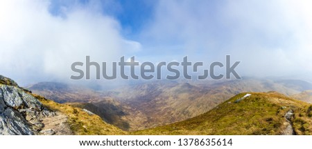 A view of a mountain valley with rocky path,grass and lake in the background under a majestic blue sky and white clouds #1378635614