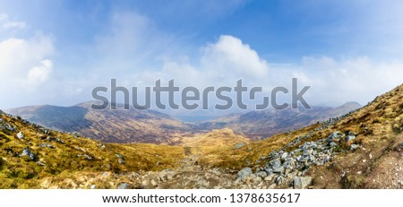 A view of a mountain valley with rocky path,grass and lake in the background under a majestic blue sky and white clouds #1378635617