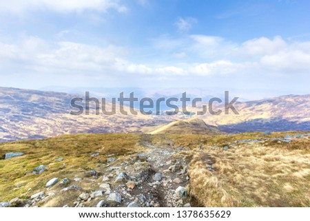 A view of a mountain valley with rocky path,grass and lake in the background under a majestic blue sky and white clouds #1378635629