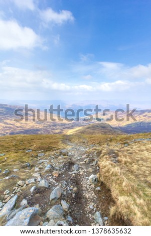 A view of a mountain valley with rocky path,grass and lake in the background under a majestic blue sky and white clouds #1378635632