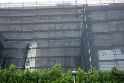 A view of a netted scaffold structure surround a building during construction.