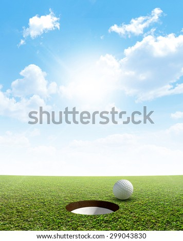 A view of a perfectly manicured golf putting green and hole with a ball on the edge in the daytime on a blue sky background