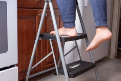 A view of a person and their feet on a two level step ladder in a kitchen setting. One foot is hanging off.